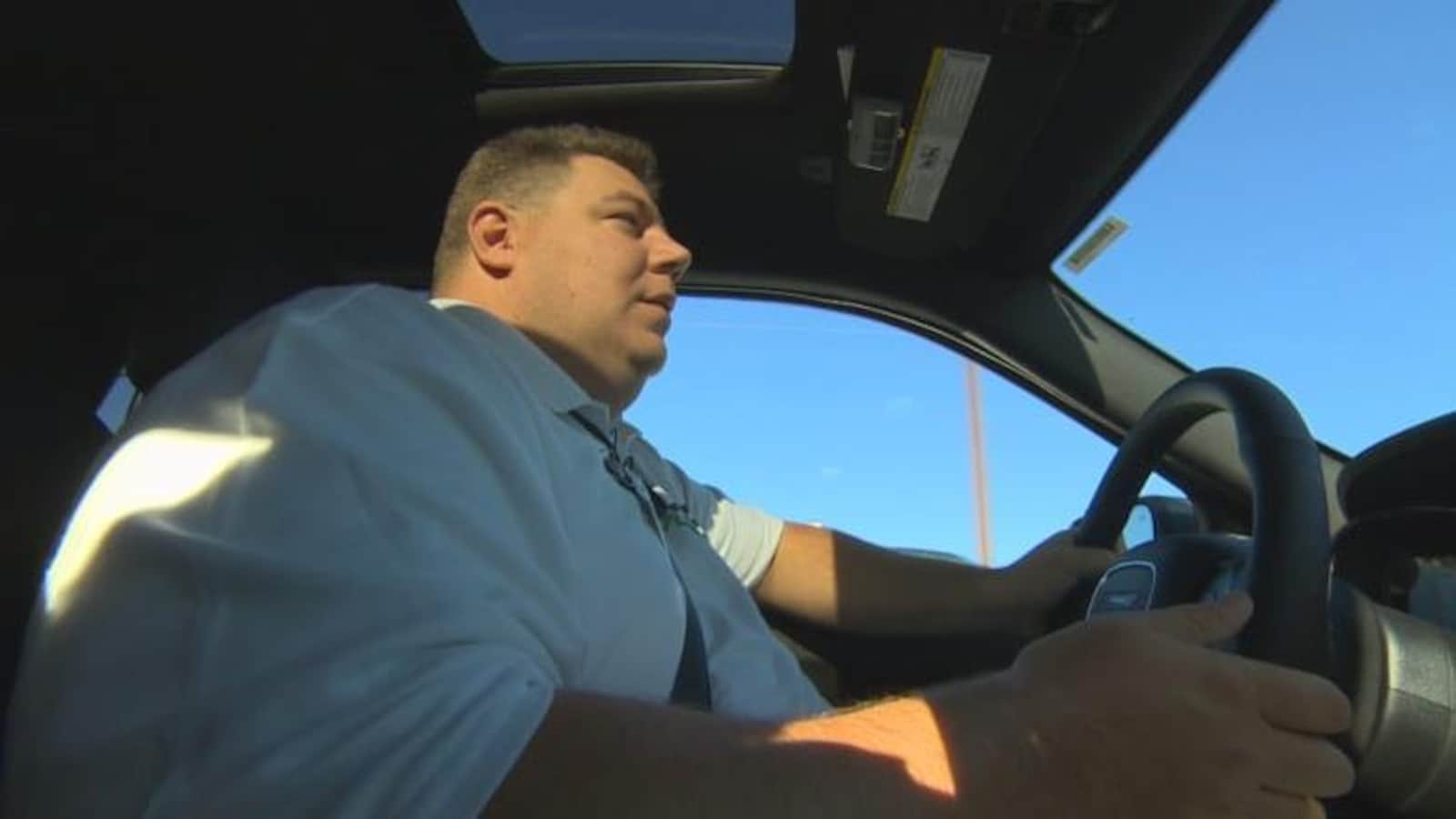 En contre-plongée, photo d'un homme de corpulence forte qui conduit un véhicule sous un ciel bleu.
