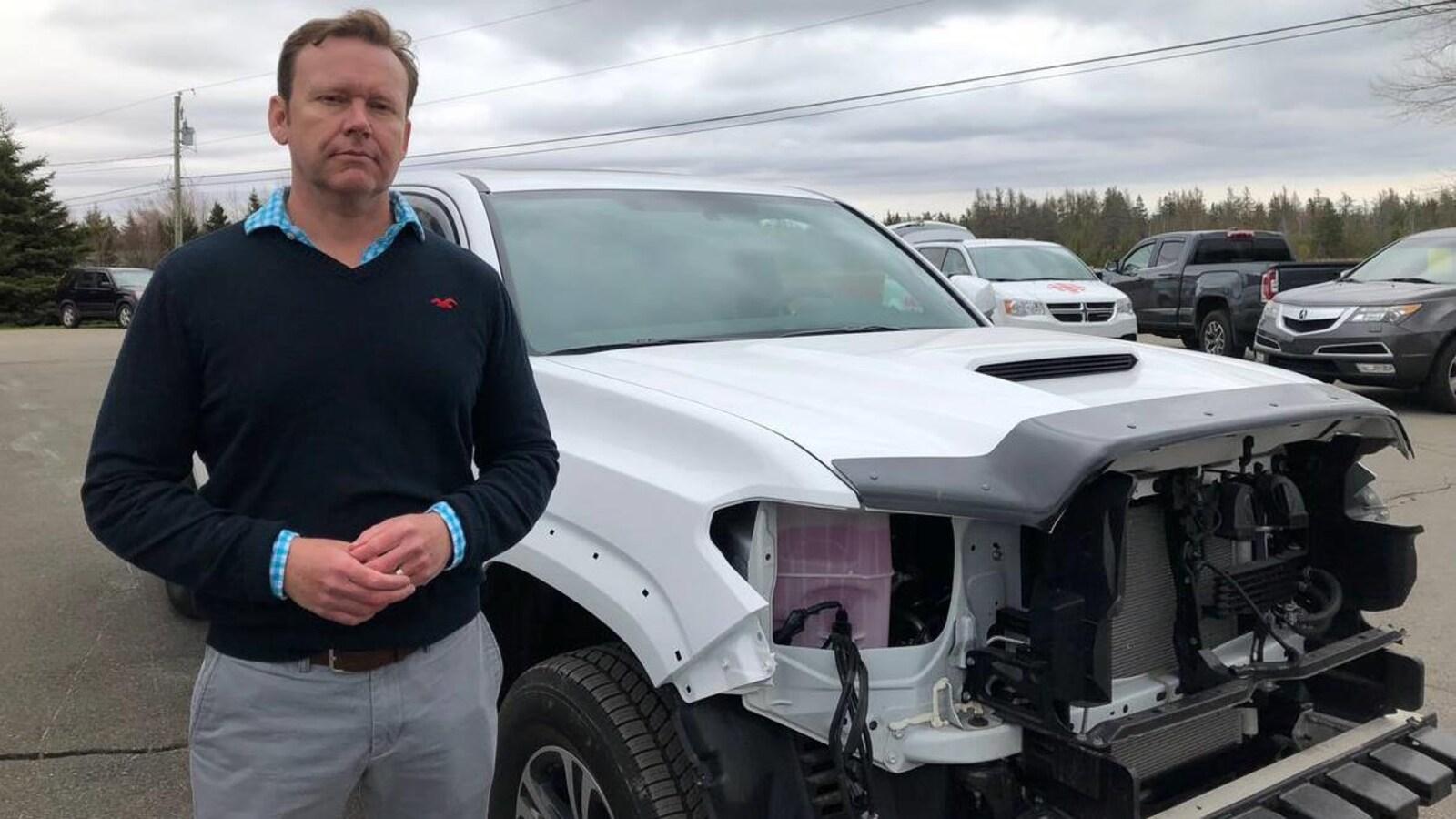 Sam Dalton debout devant sa camionnette qui n'a plus de phares ni de radiateur