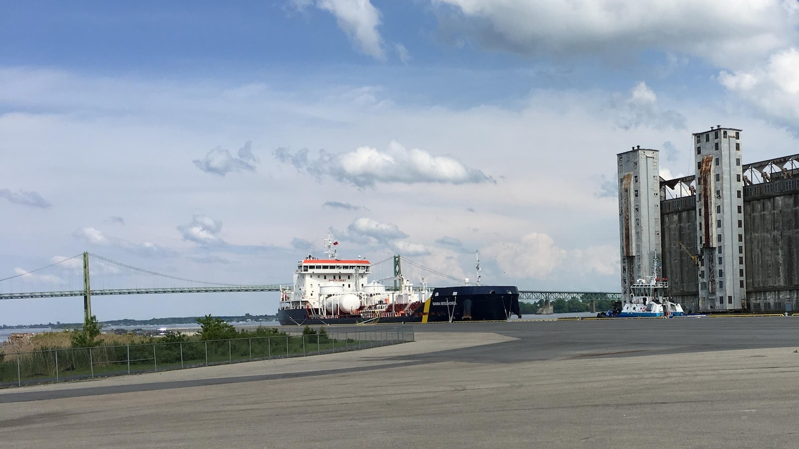 Un pétrolier sur le bord de la rive devant un pont