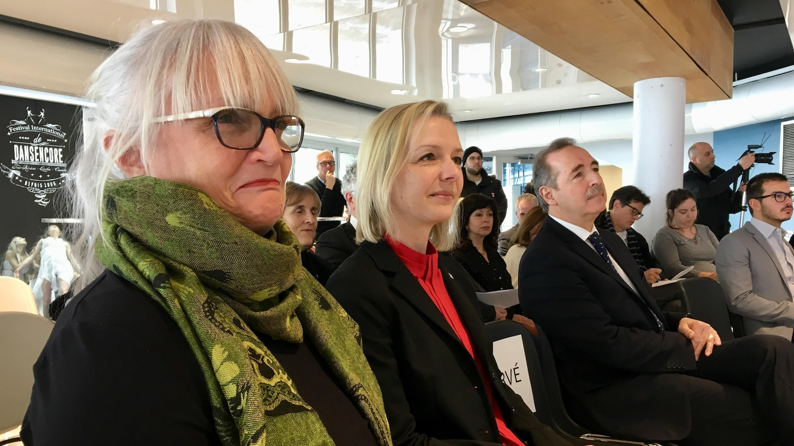 Deux femmes regardent une conférence de presse. L'une d'elle porte des lunette et un foulard.
