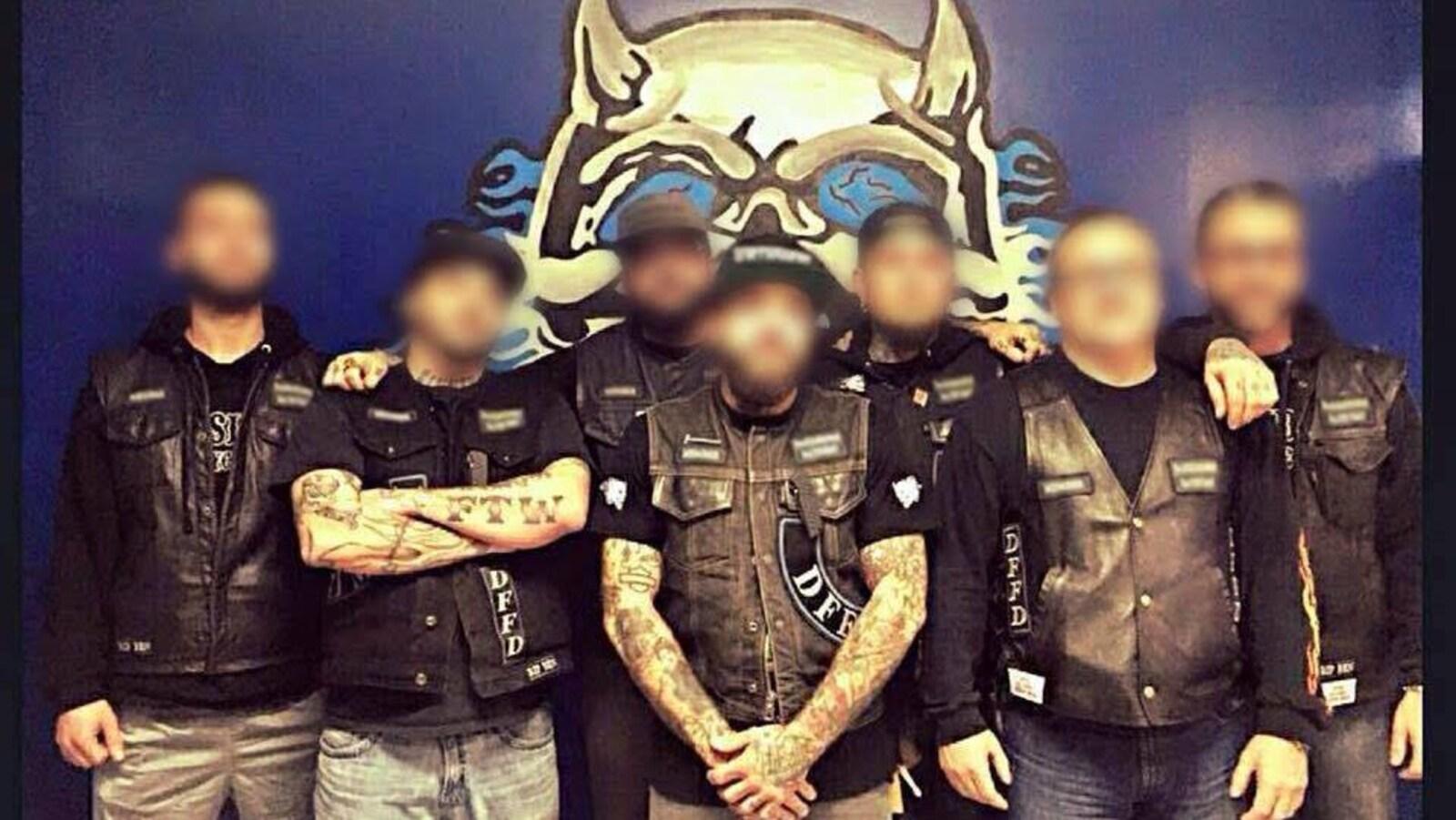 Les membres du groupe de motards Darksiders North Shore prennent la pose devant une affiche du groupe. Leurs visages sont brouillés.