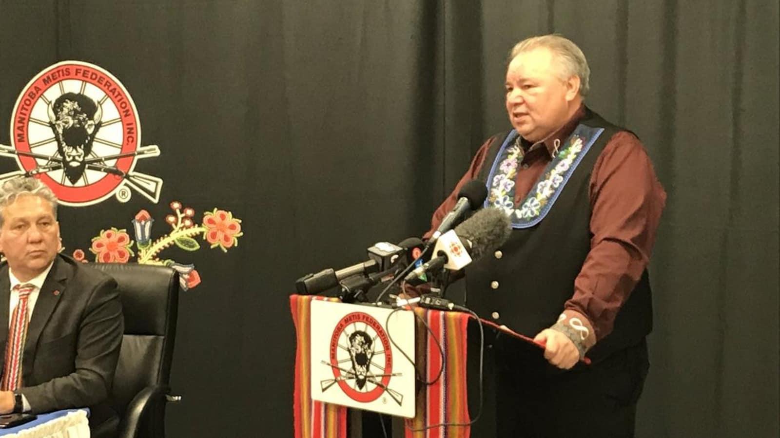Un homme se tient à un podium dans le cadre d'une conférence de presse.