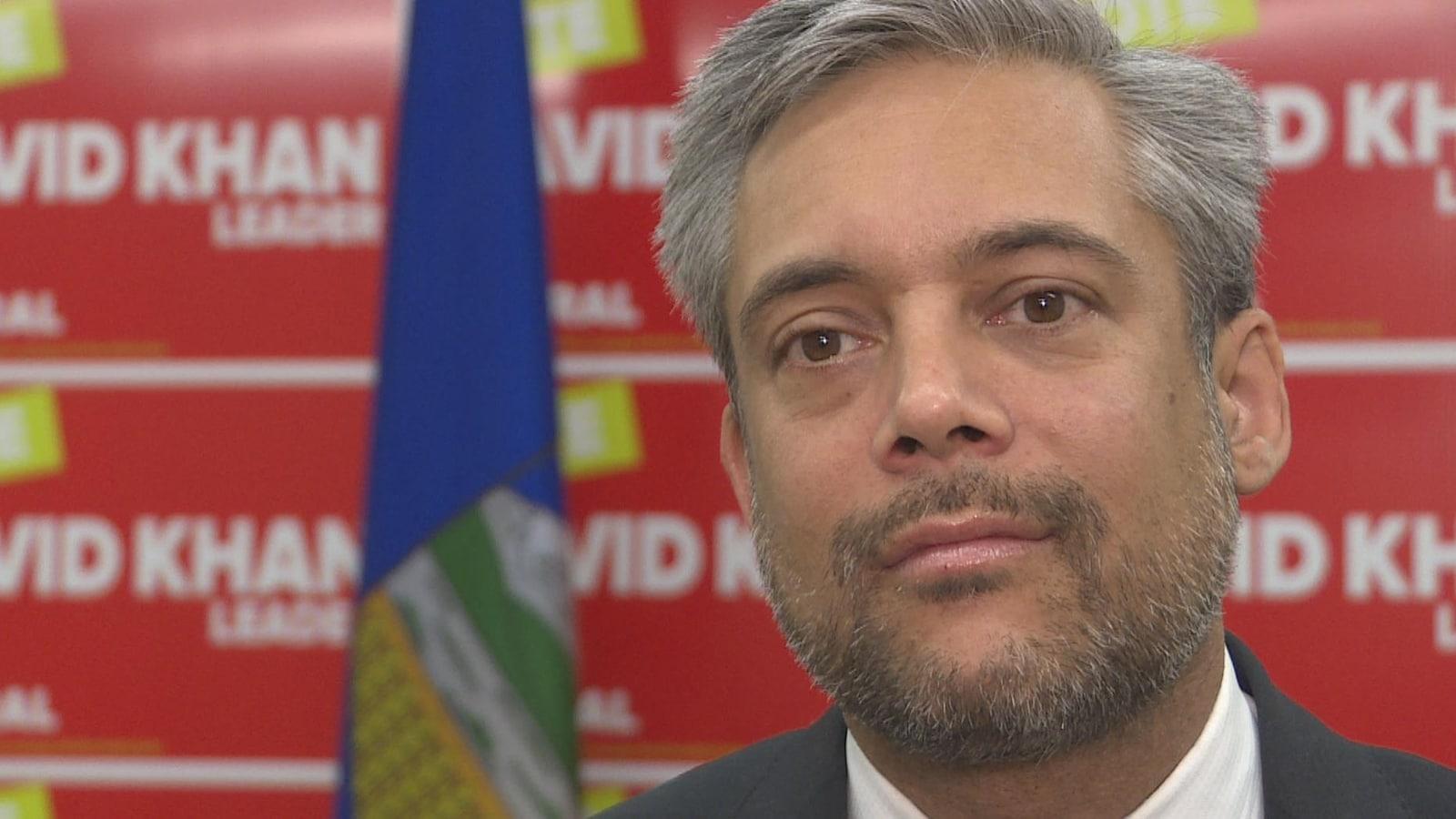 Le chef du Parti libéral de l'Alberta, David Khan, derrière un drapeau et des pancartes dans son bureau à Calgary.
