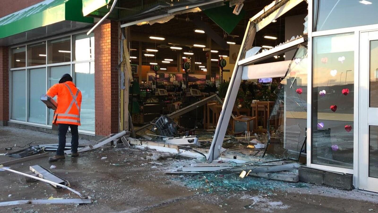 Un employé debout devant le magasin Sobeys du chemin Kelsey de Saint-Jean, entouré de débris.