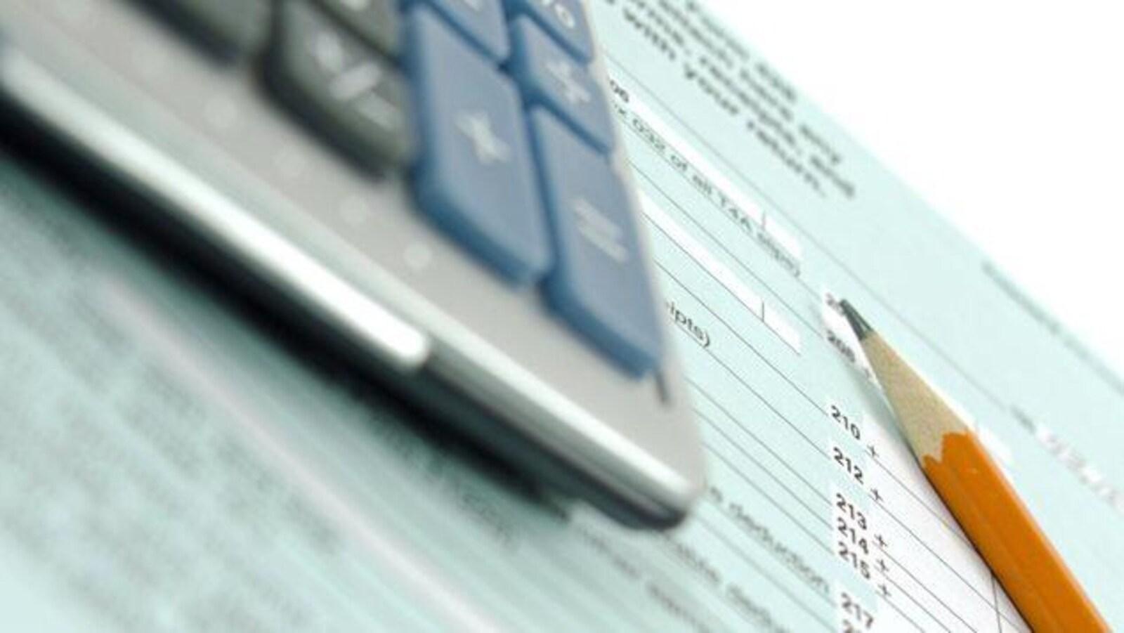 Une déclaration de revenus, une calculatrice et un crayon.