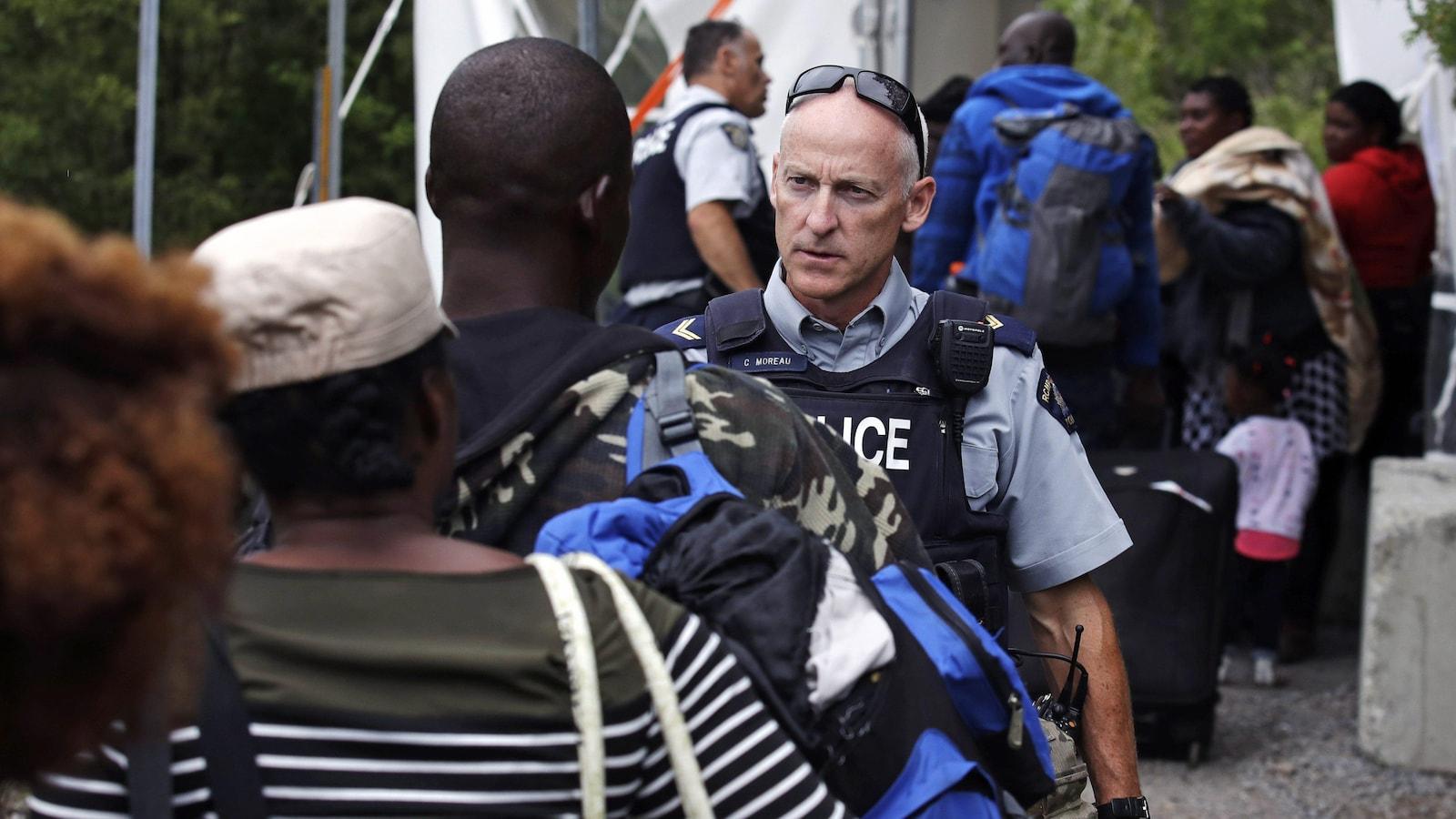 Un employé de la Gendarmerie royale du Canada (GRC) accueille des demandeurs d'asile à la frontière canado-américaine à Saint-Bernard-de-Lacolle.