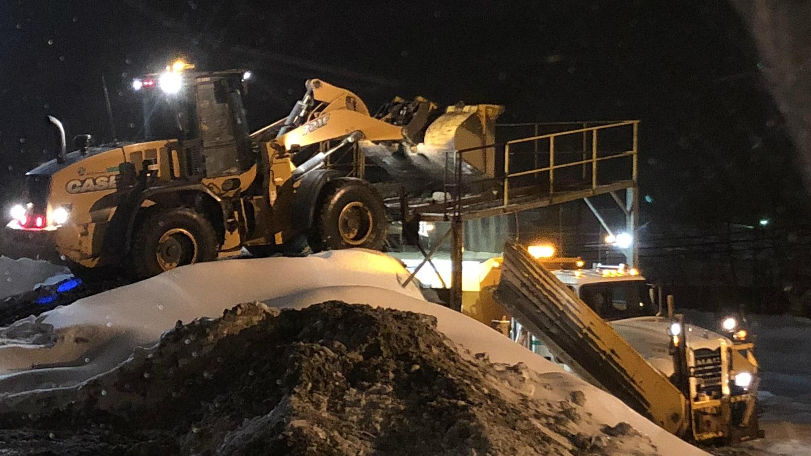 Deux camions de déneigement travaillent de nuit.