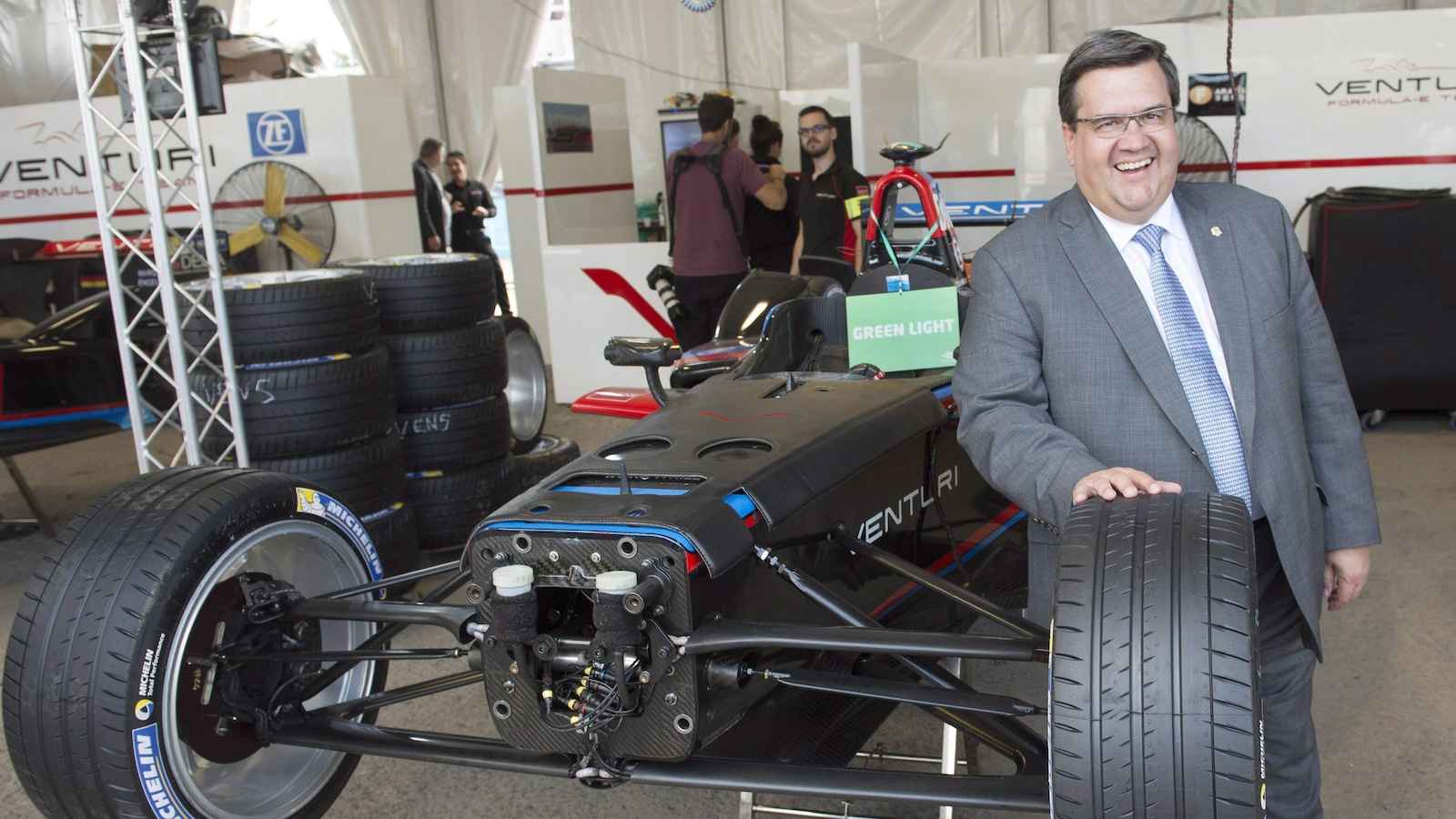M. Coderre se tient debout à côté d'une voiture de course, posant la main sur l'un de ses pneus.