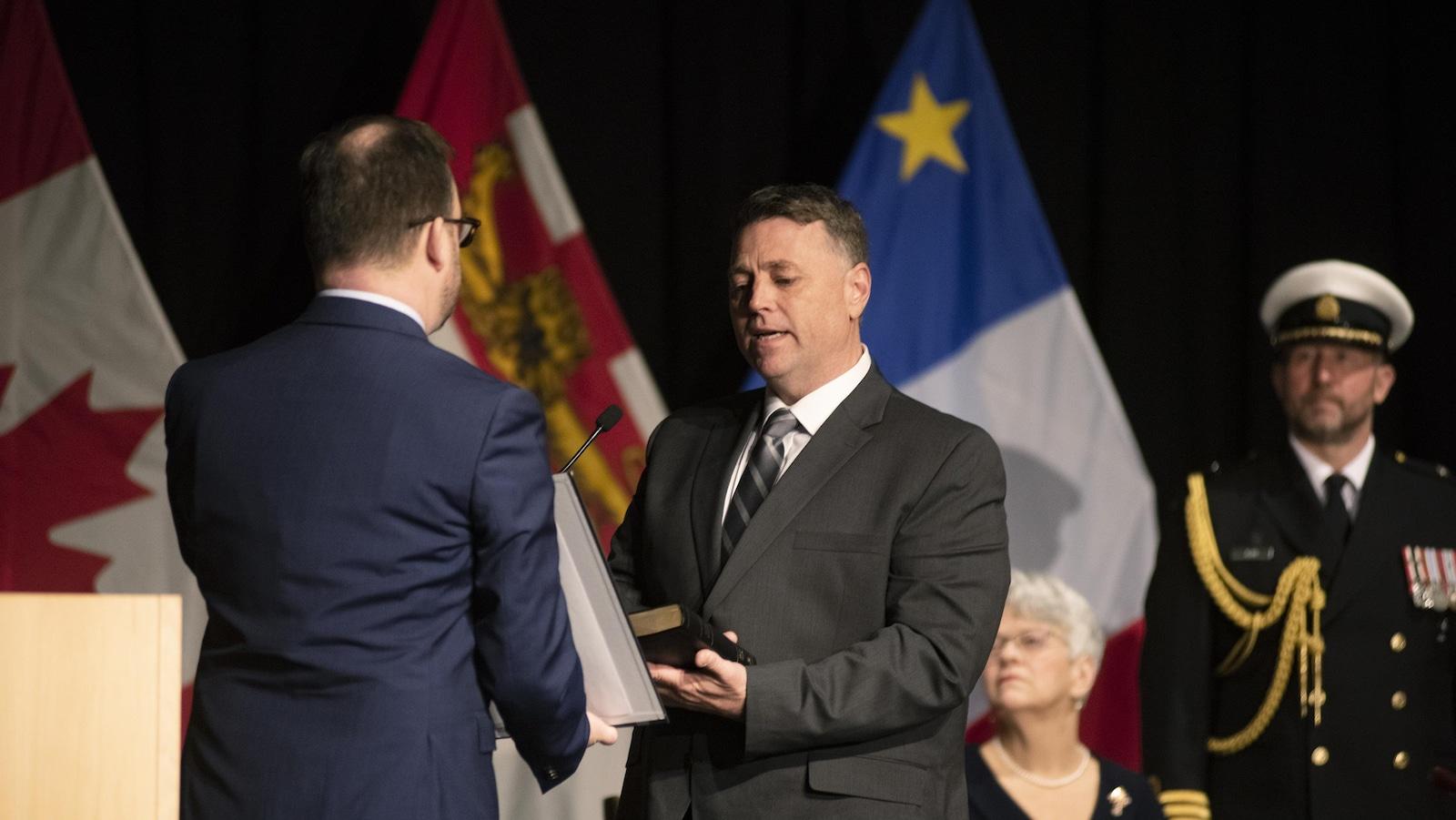 Deux hommes se tiennent debout sur une scène, face à face, devant des drapeaux, et l'homme à droite lit un serment en tenant une bible.