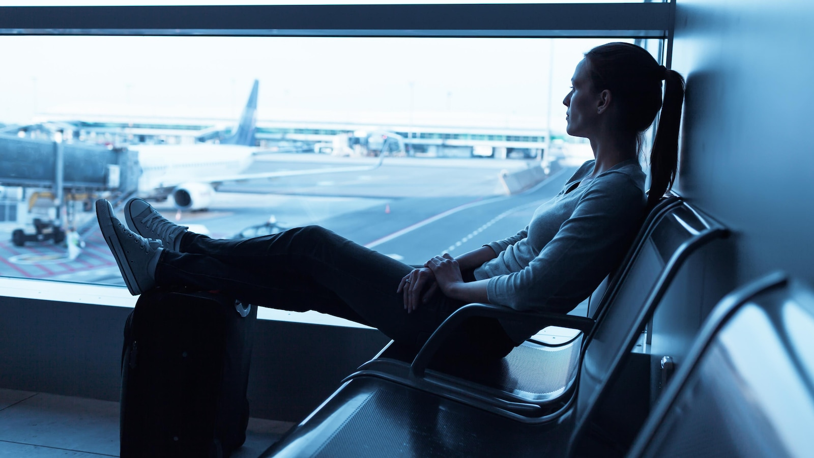 Une femme regarde à travers la fenêtre à l'aéroport