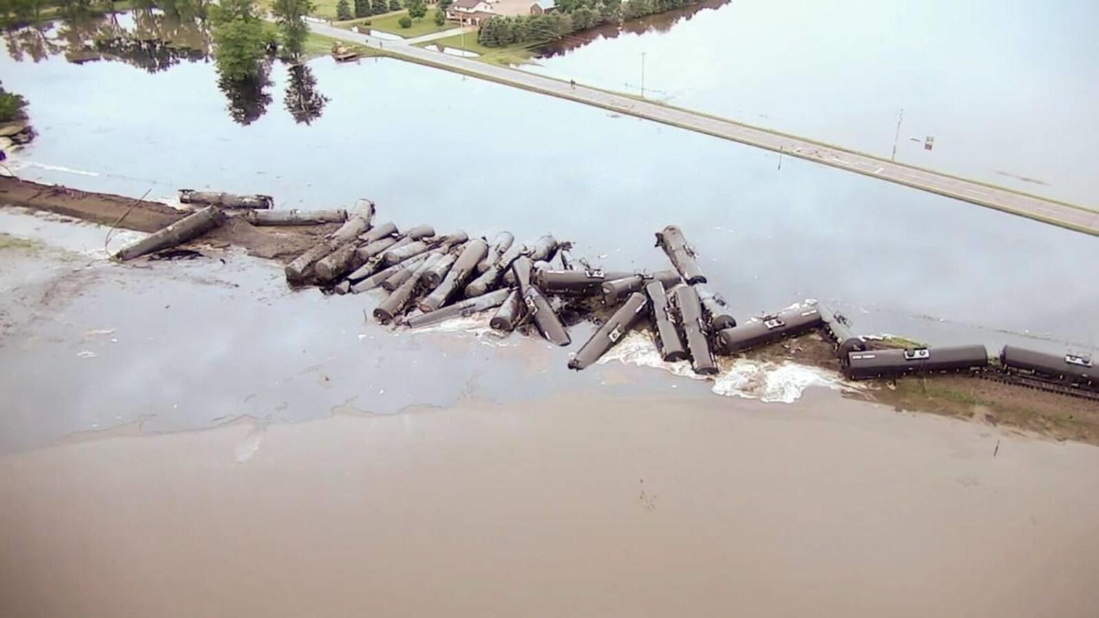 Vue aérienne d'une trentaine de wagons-citernes qui sont empilés sur une voie ferrée inondée.