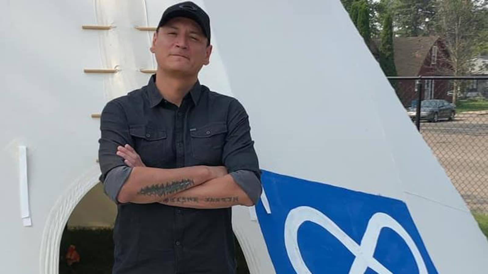 Un homme se tient les bras croisés à l'entrée d'un tipi sur lequel est dessiné le signe métis.