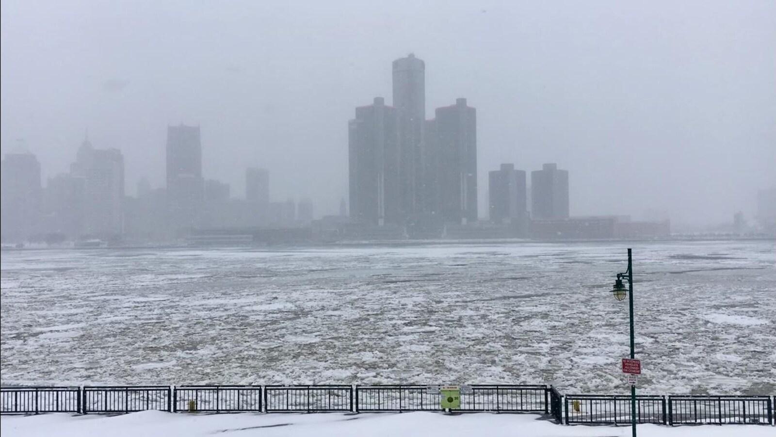 Rivière en partie glacée et centre-ville sous la neige.
