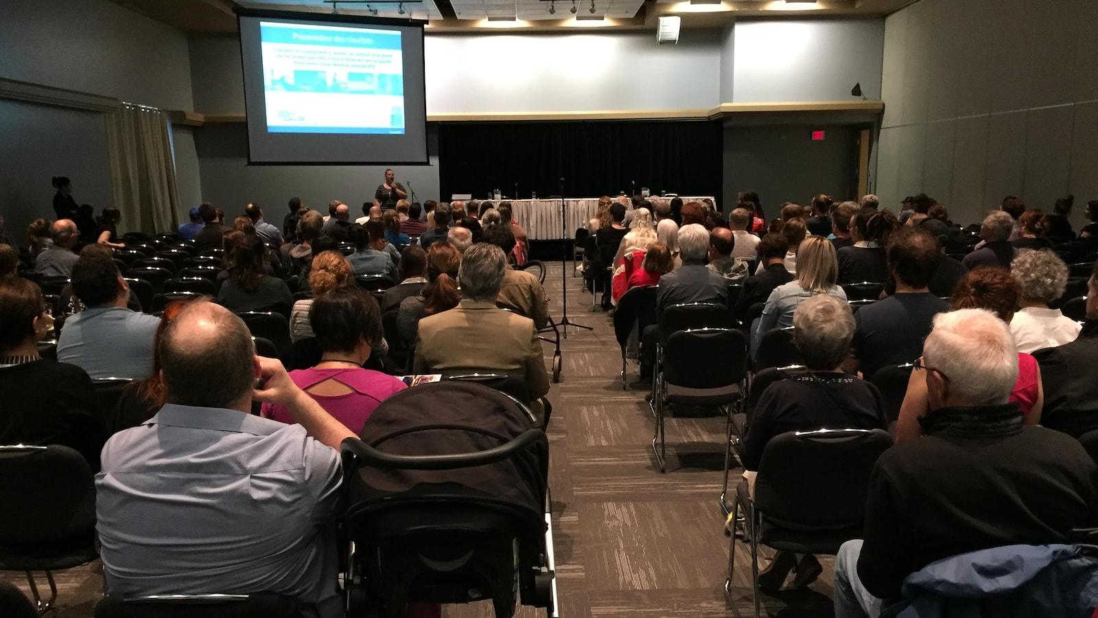 Plusieurs dizaines de citoyens écoutent une présentation dans une salle de congrès.
