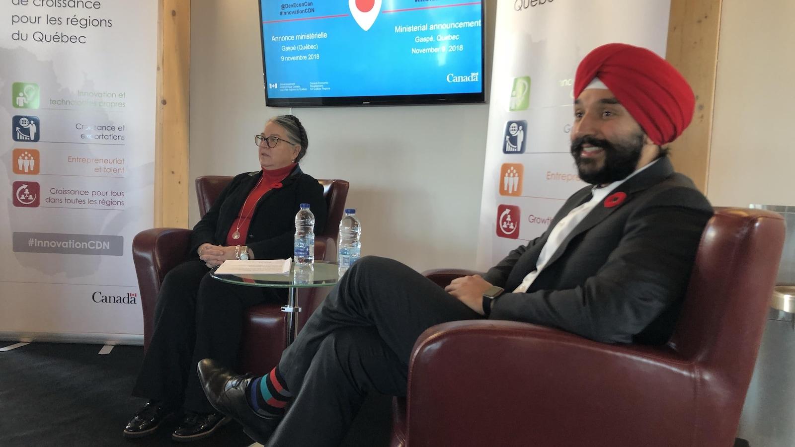 Une femme assise dans un fauteuil brun et un homme assis dans un fauteuil rouge