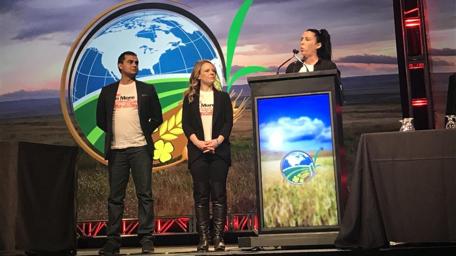 Les trois fondateurs son sur une scène où on voit en arrière-plan un grand champ et une carte de l'amérique du nord, une femme se tient derrière le podium de la conférence FarmTech.
