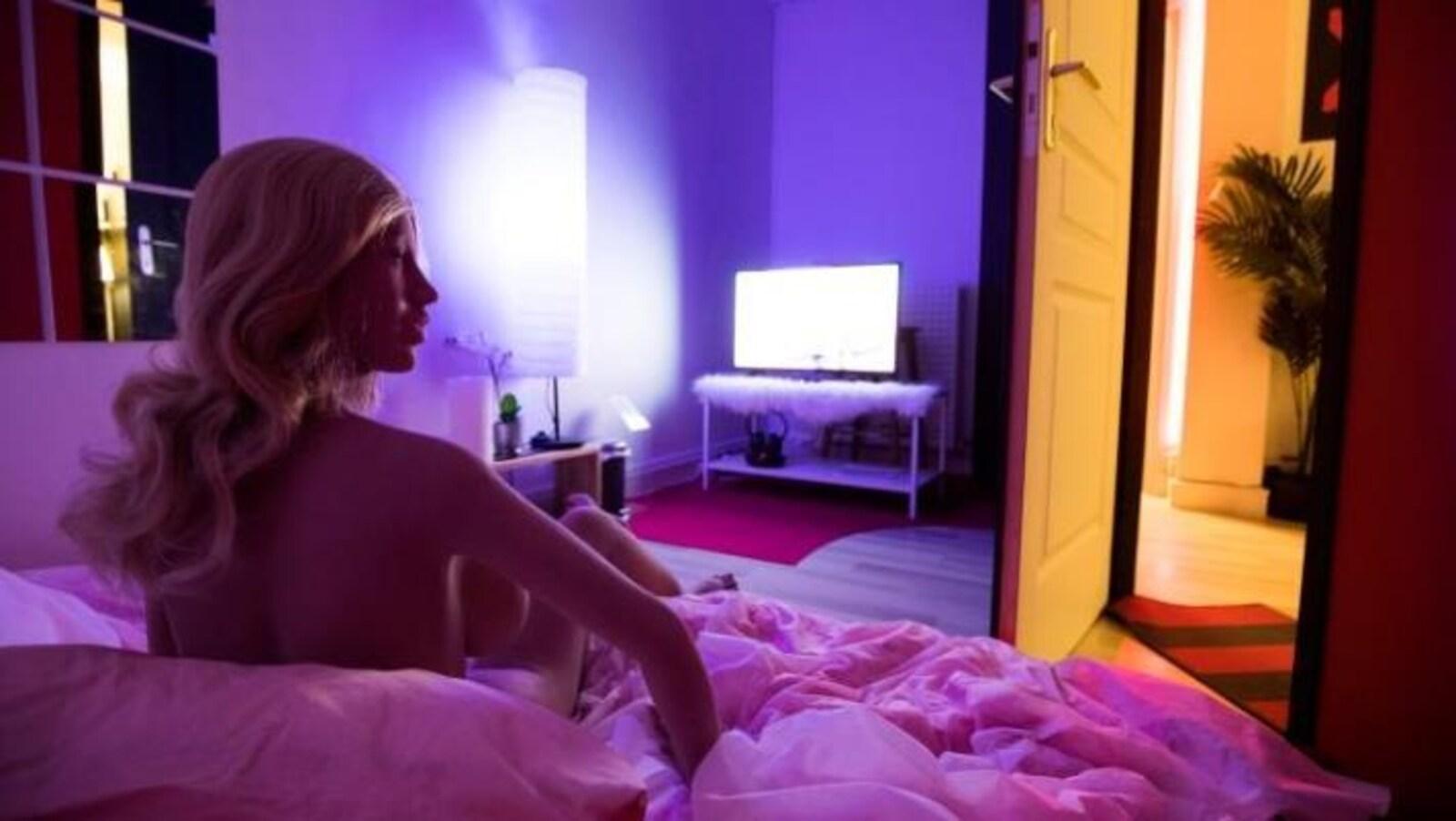 une poupée en silicone nue sur un lit, blonde, regarde la télé