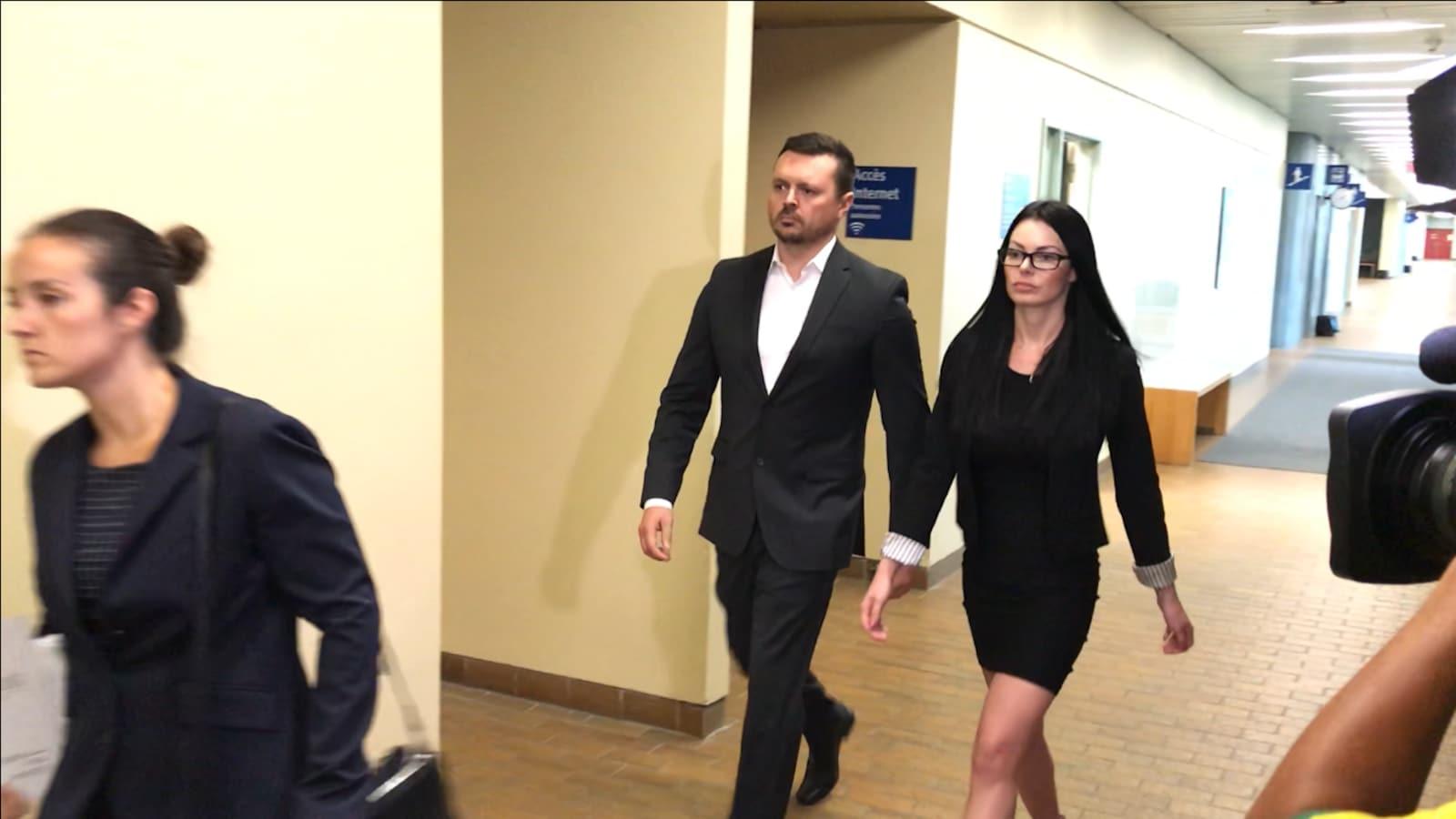 Dominic Lacroix et sa conjointe marchent dans les couloirs du palais de justice de Québec.