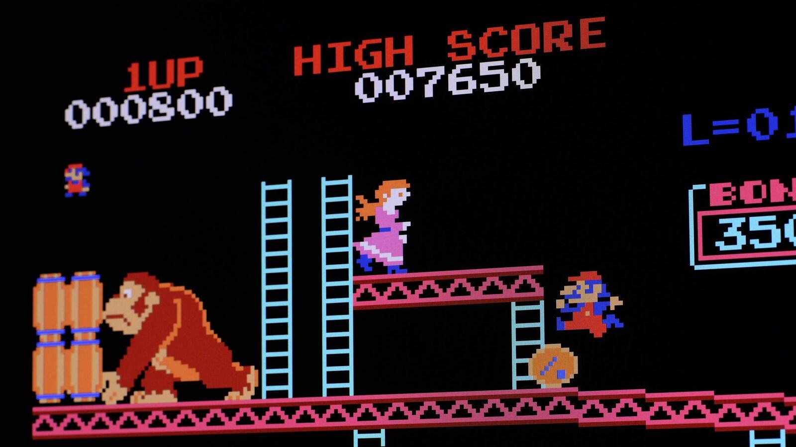 Une capture d'écran du jeu vidéo d'arcade Donkey Kong montrant un gorille en train d'attraper un baril de bois dans une pile, pendant que le personnage de Mario saute par dessus un autre baril. Un personnage féminin habillé d'une robe rose regarde vers Mario du haut d'une plate-forme.