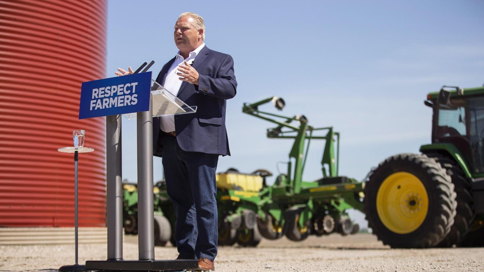 Un homme derrière un lutrin avec des tracteurs derrière lui