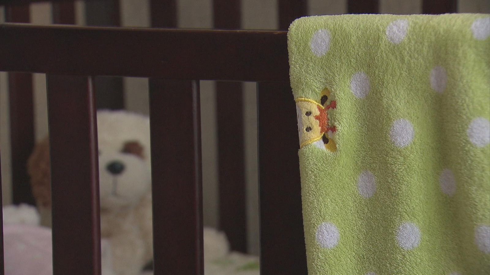 Un lit d'enfant avec une couverture verte. En arrière, se trouve une peluche.