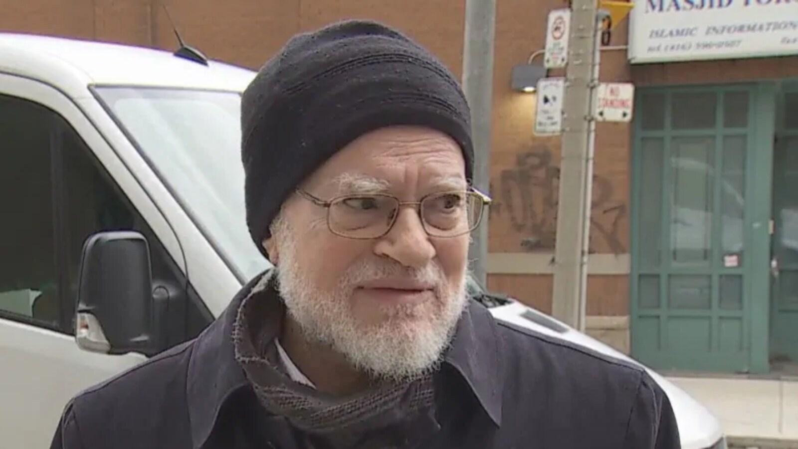 Le Dr El Tantawy Attia répond aux questions des journalistes, il a une barbe blanche, des lunettes de vue et porte une tuque.