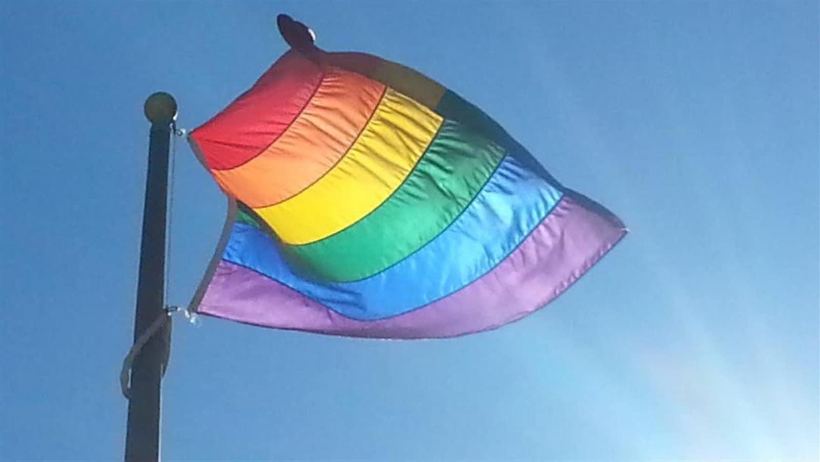 Un drapeau multicolore flotte au vent.