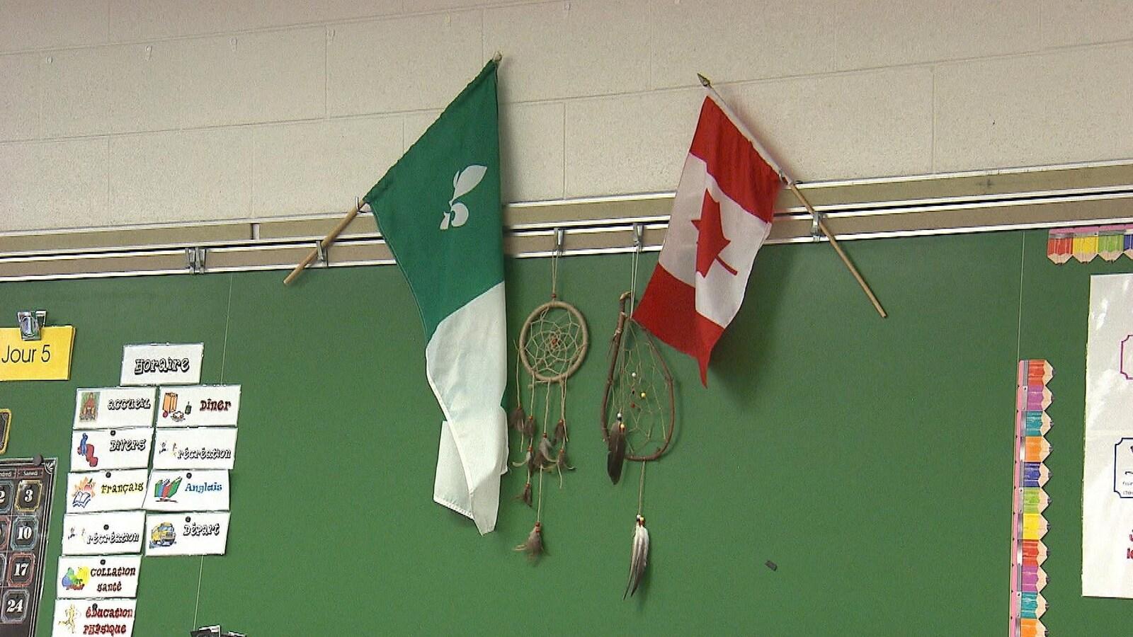 Les drapeaux franco-ontarien et canadien accrochés au-dessus du tableau d'une classe.