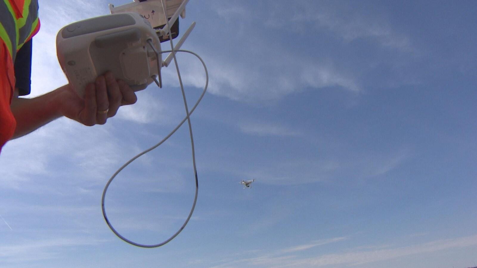 Au premier plan à gauche : les mains d'un pilote de drone manipulent une télécommande. Au fond, en arrière-plan : un drone blanc vole dans le ciel.