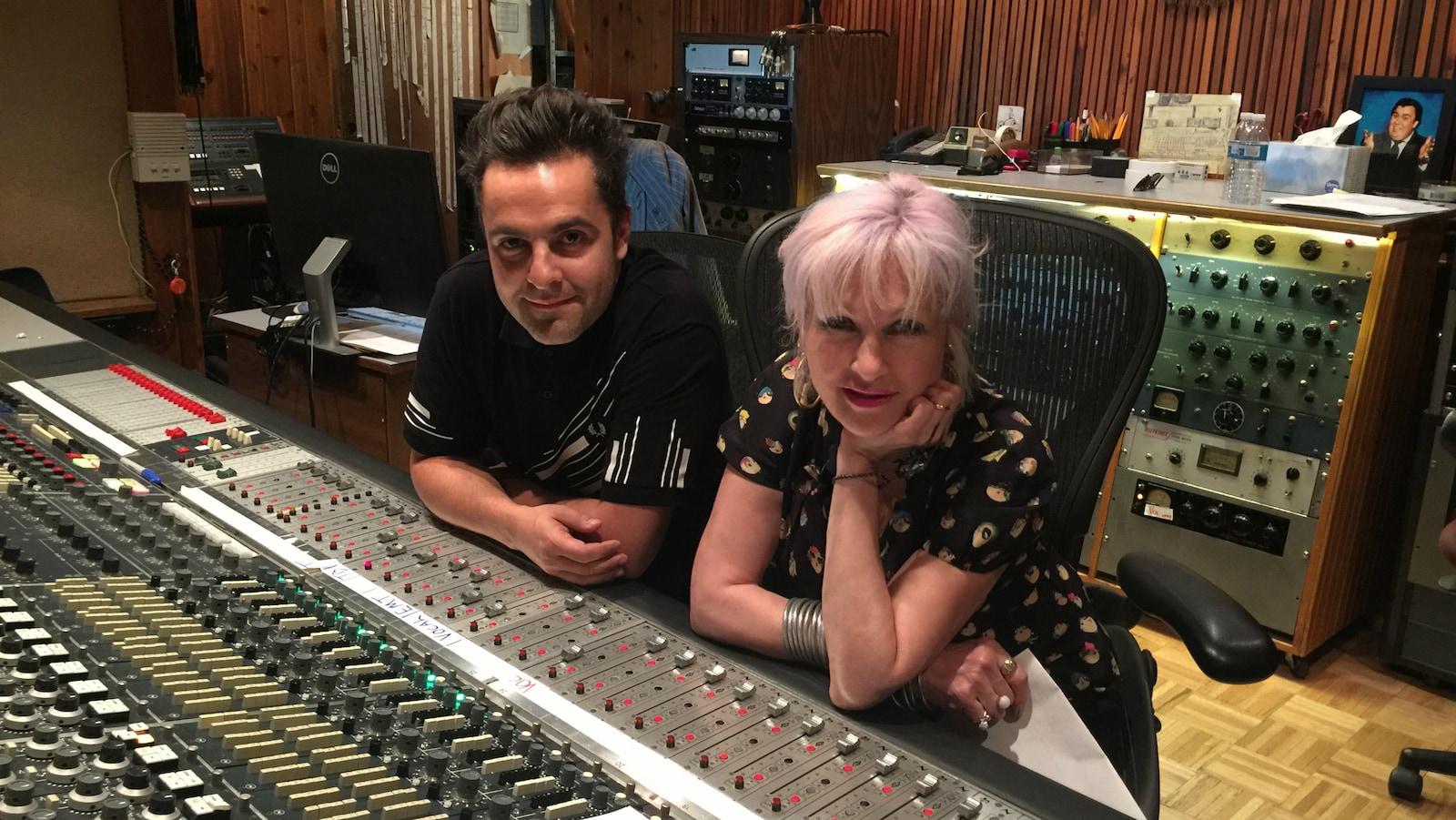 Dumas et Cyndi Lauper, assis côte à côte, devant une console d'un studio d'enregistrement.