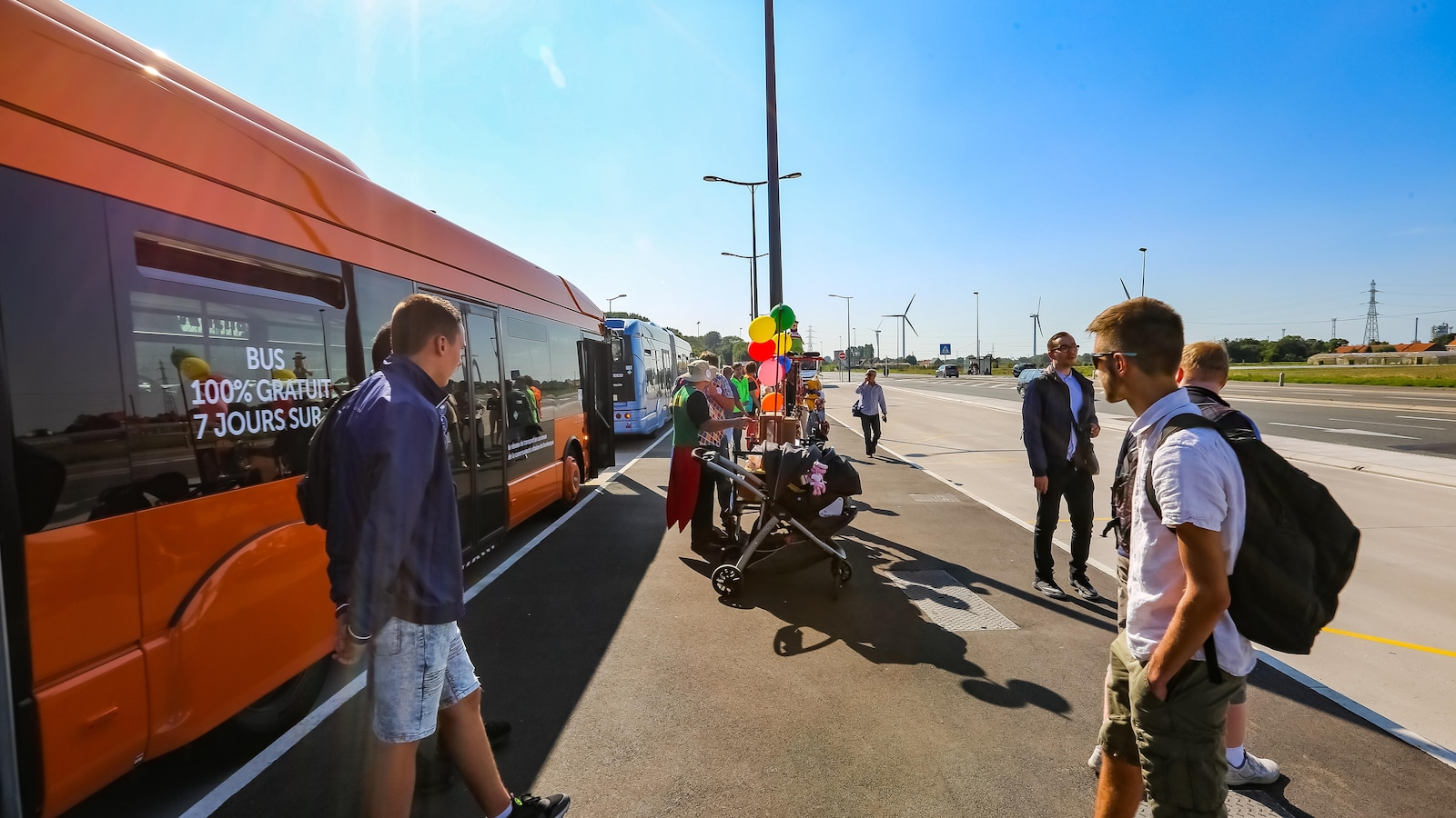 Des utilisateurs du réseau d'autobus de transport de Dunkerque circulent dans un pôle d'échange.