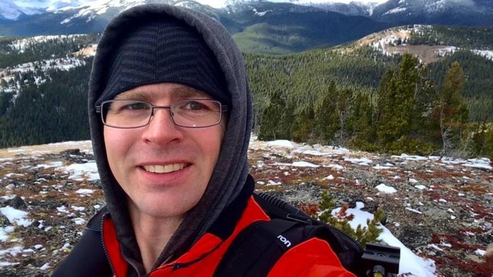 Plan serré du visage de Dwayne Schnell habillé pour la randonnée avec en arrière-plan des montagnes et une forêt en hiver.