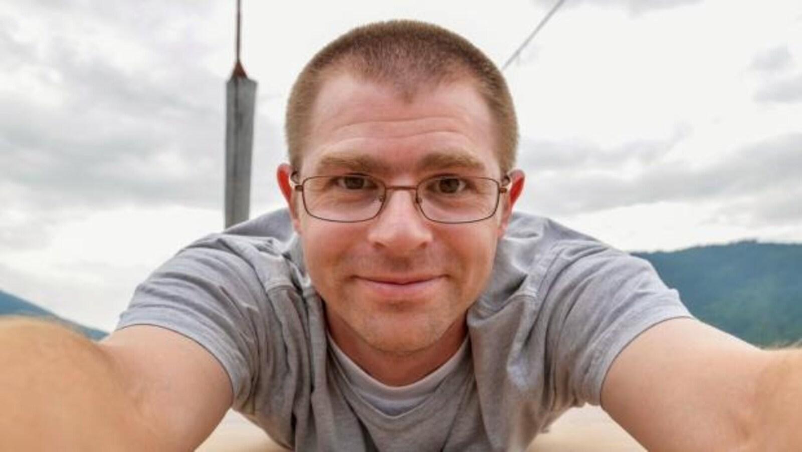 Dwayne Schnell se penche vers la caméra et sourit.