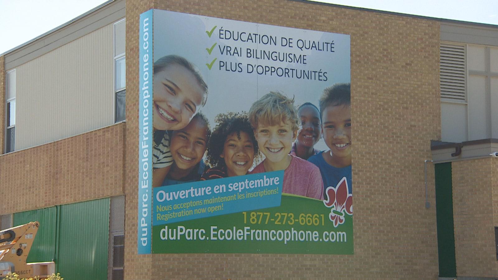 Un mur d'école en briques avec une grande affiche qui montre des jeunes souriants. Il est écrit que l'école ouvre en septembre.