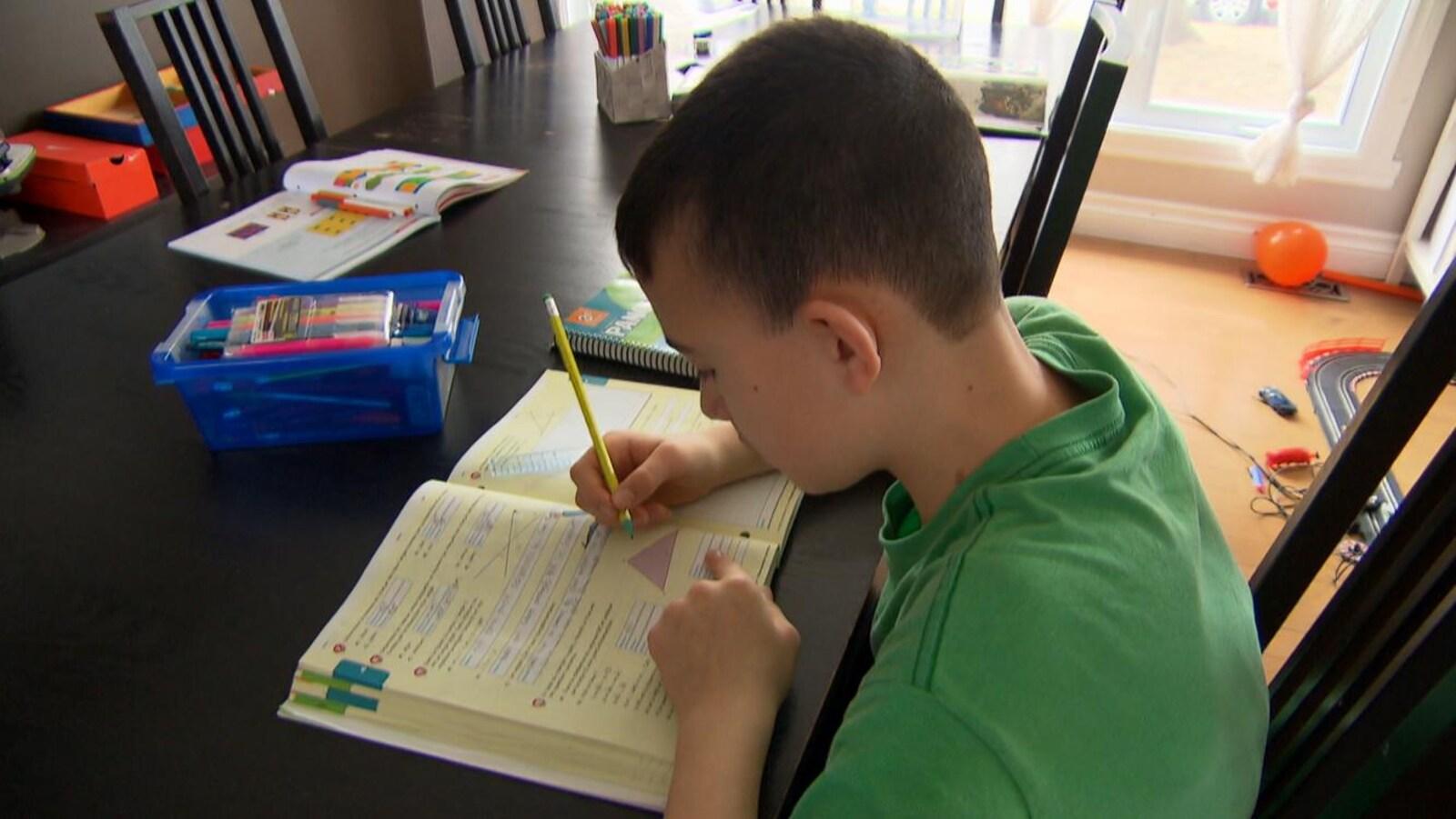 Un jeune garçon fait ses devoirs sur la table de la maison familiale.