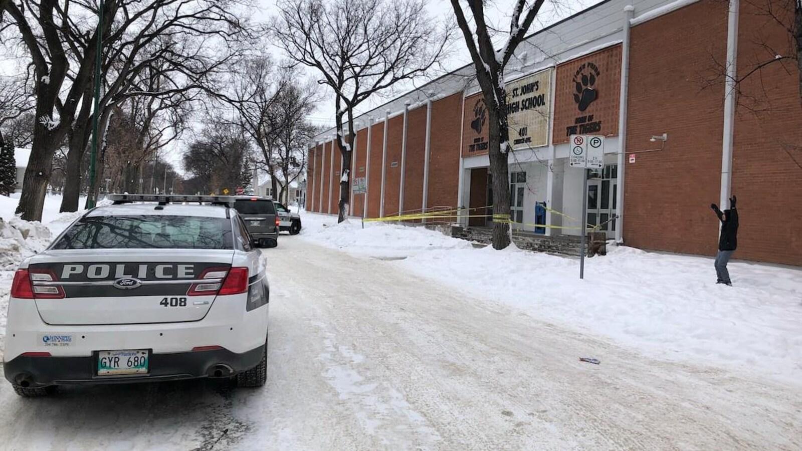 Des voitures de police sont stationnées sur la rue, devant une école.