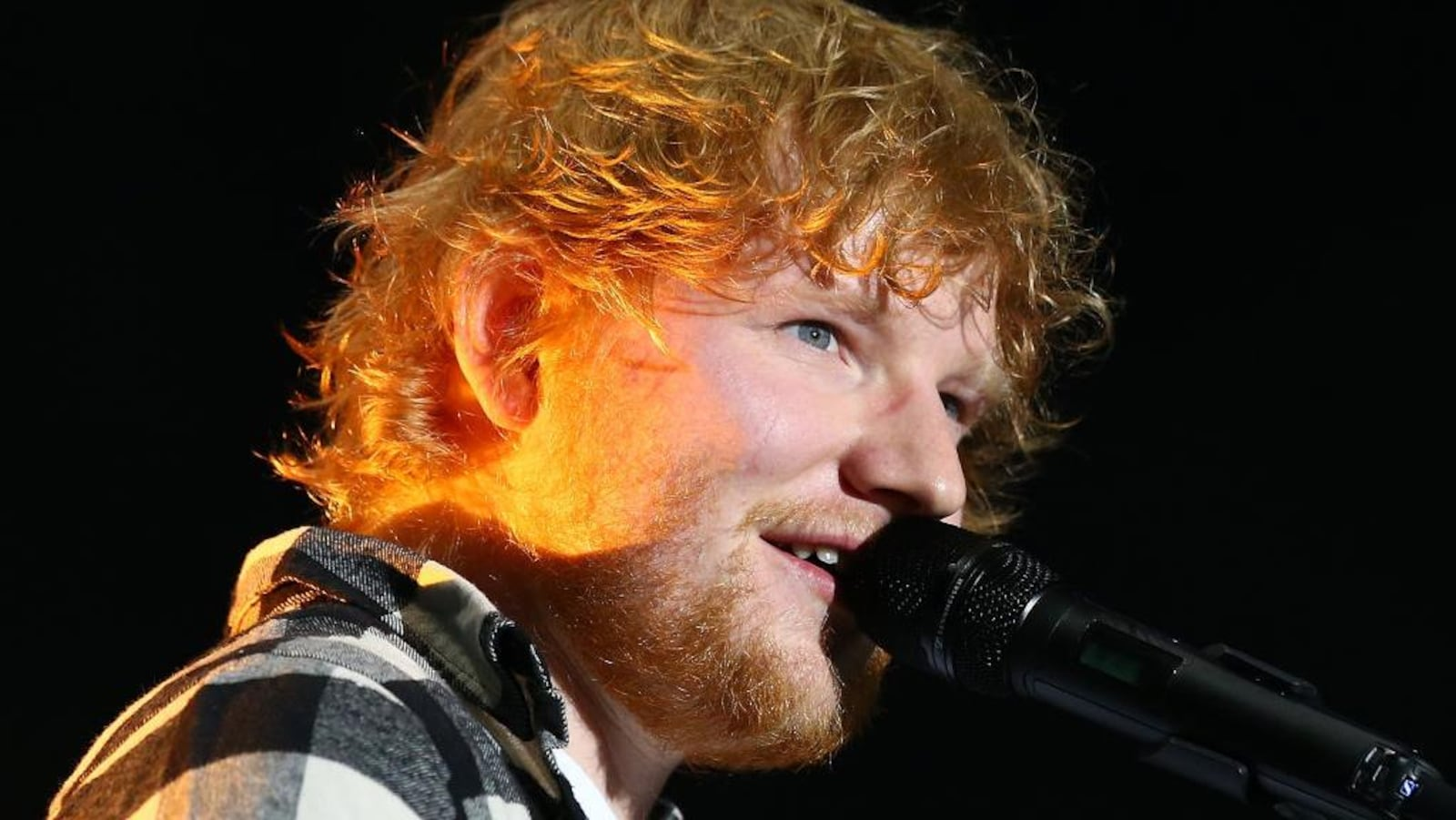 L'artiste britannique Ed Sheeran chante au micro.