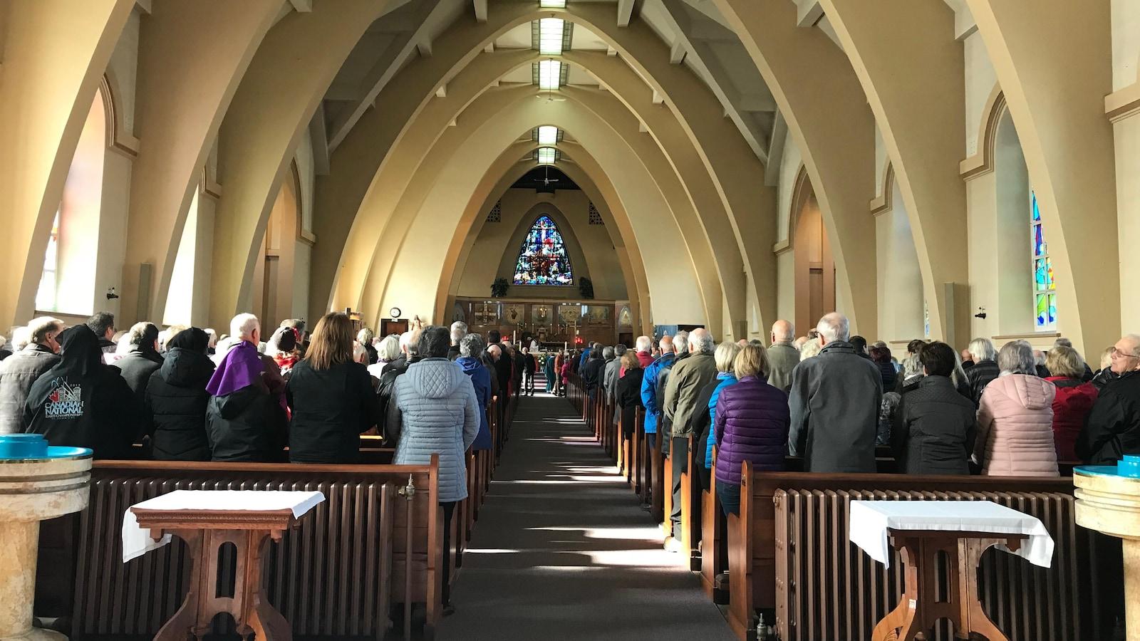 Les paroissiens et paroissiennes se tiennent debout dans l'église.