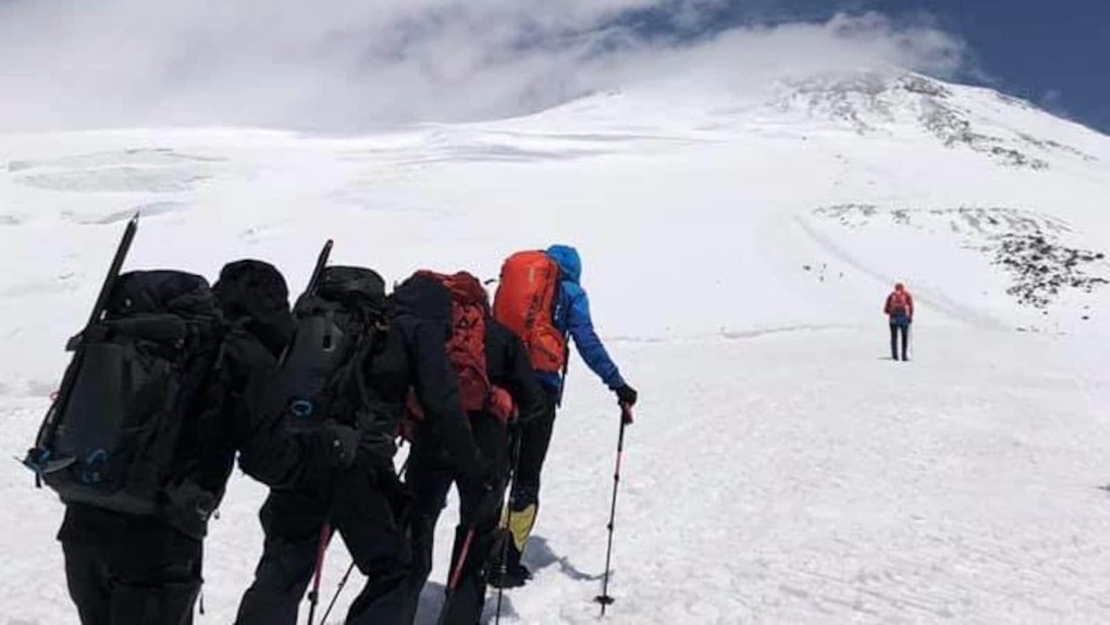 Des alpinistes grimpent vers le sommet enneigé d'une montagne.