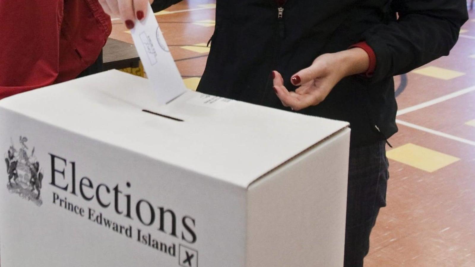 Une femme glisse un bulletin de vote dans la fente d'une boîte de scrutin.