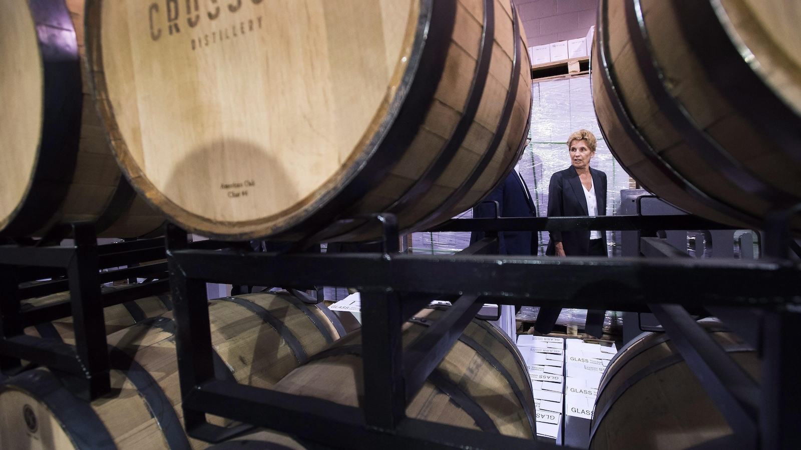 Ontario Liberal Leader Kathleen Wynne is framed between aging barrels before speaking at Crosscut Distillery during a campaign stop in Sudbury, Ont., on Wednesday, May 23, 2018. THE CANADIAN PRESS/Nathan Denette
