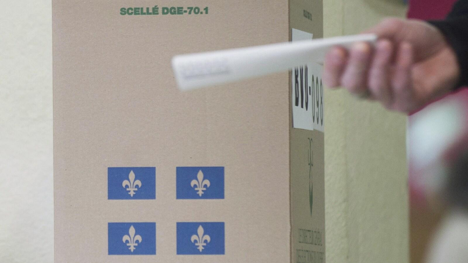 Un électeur dirige son bulletin de vote vers une boîte de scrutin.