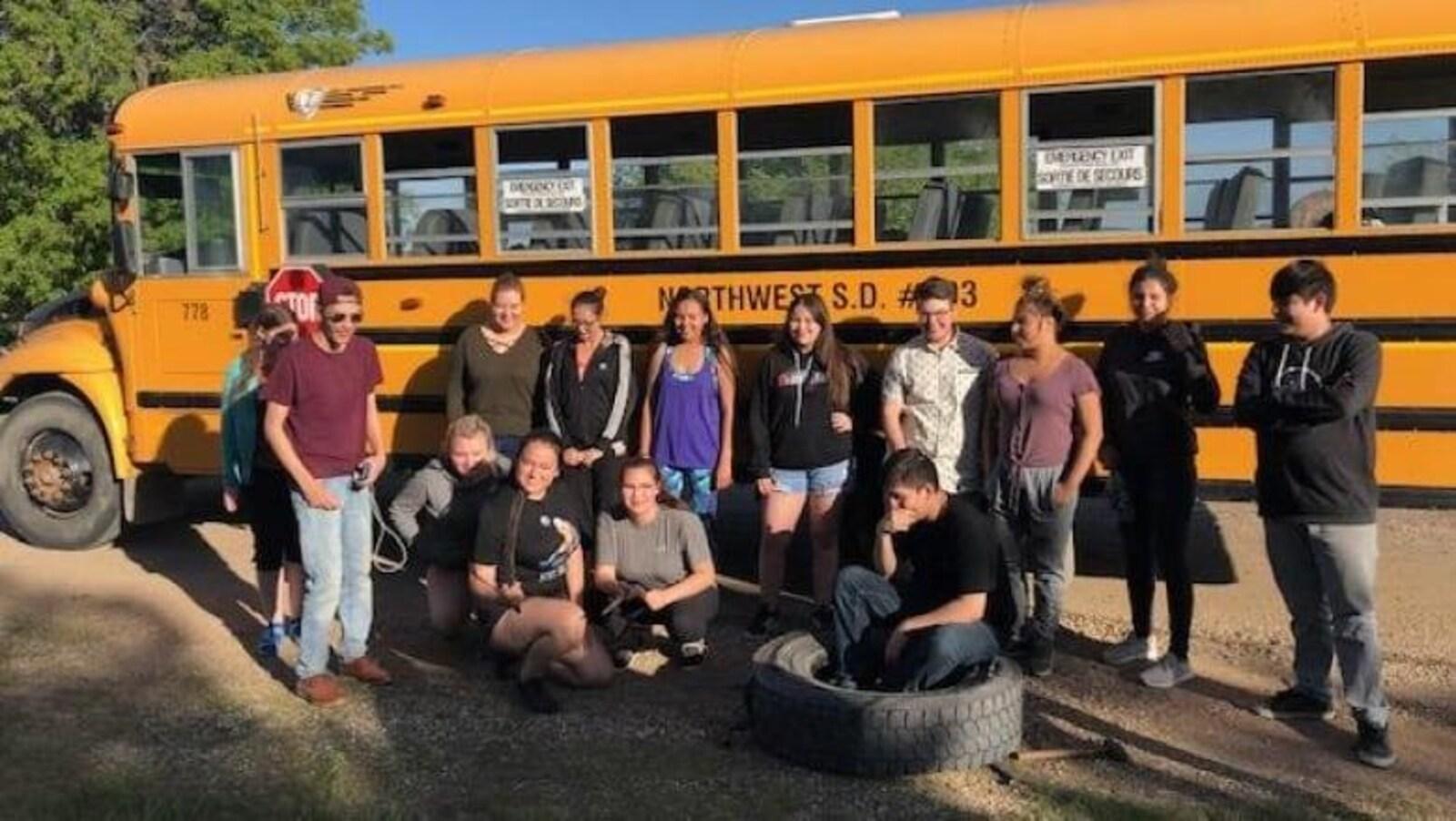 Les élèves, dans l'adolescence, posent pour une photo près de l'autobus en panne.