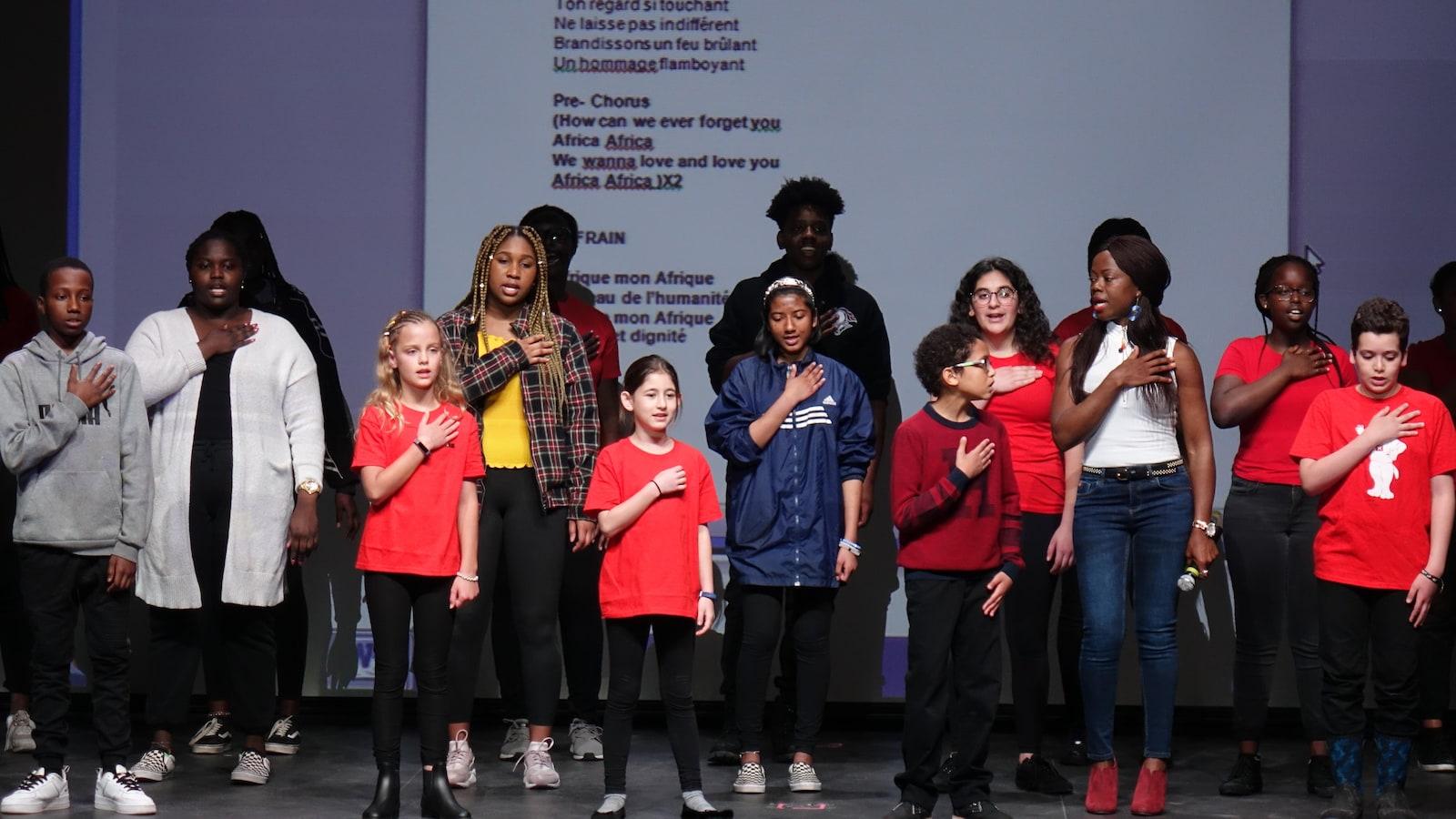 Une groupe de jeunes d'origines ethniques différentes chantent sur une scène.