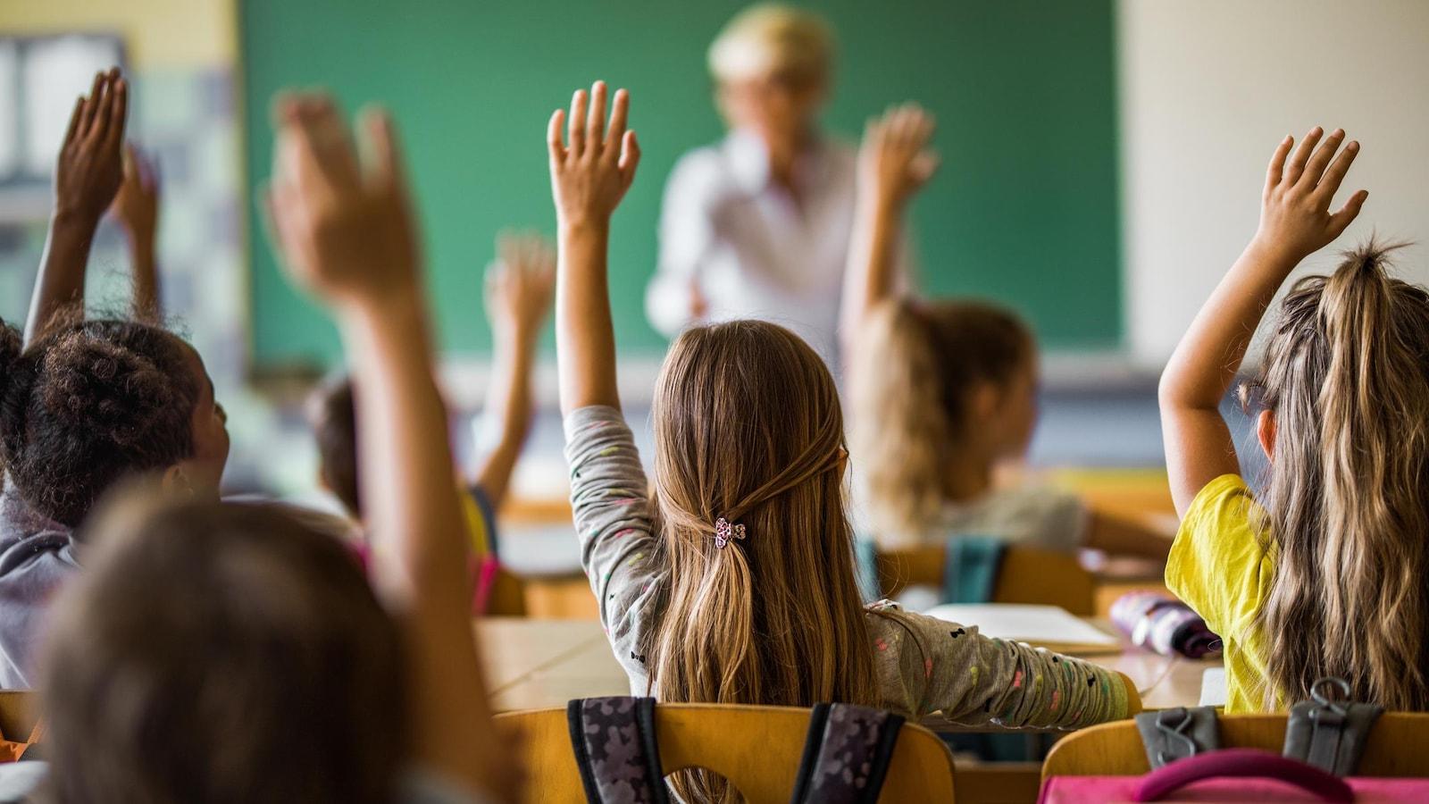 Des élèves lèvent la main dans une classe.