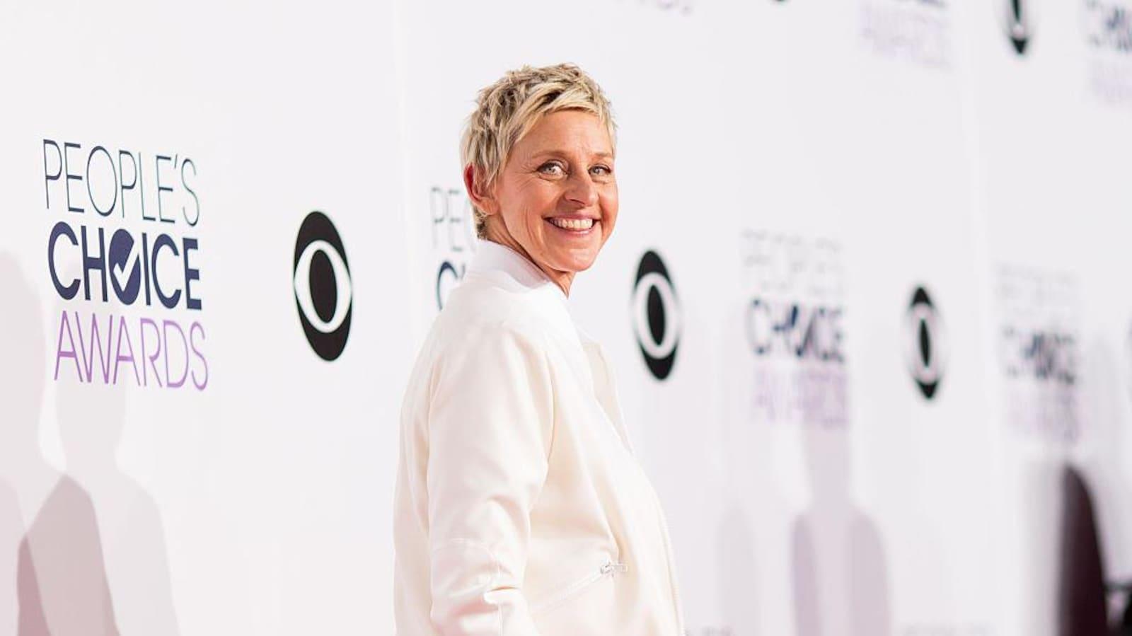 Ellen DeGeneres pose vêtue de blanc.