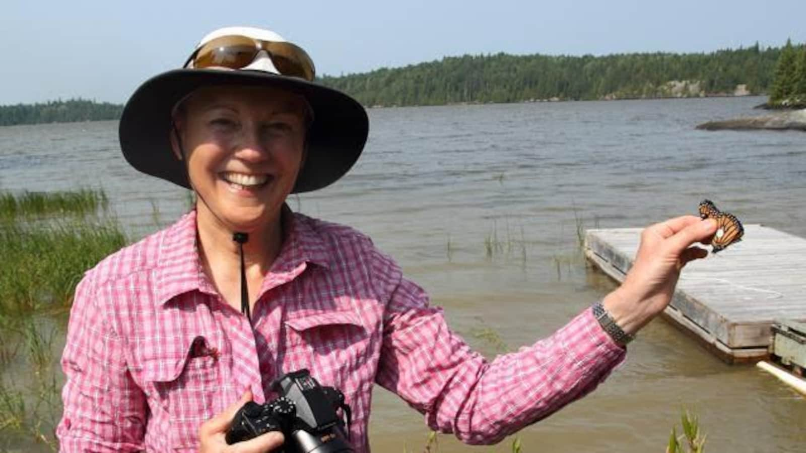 Une femme tenant un monarque devant un lac.