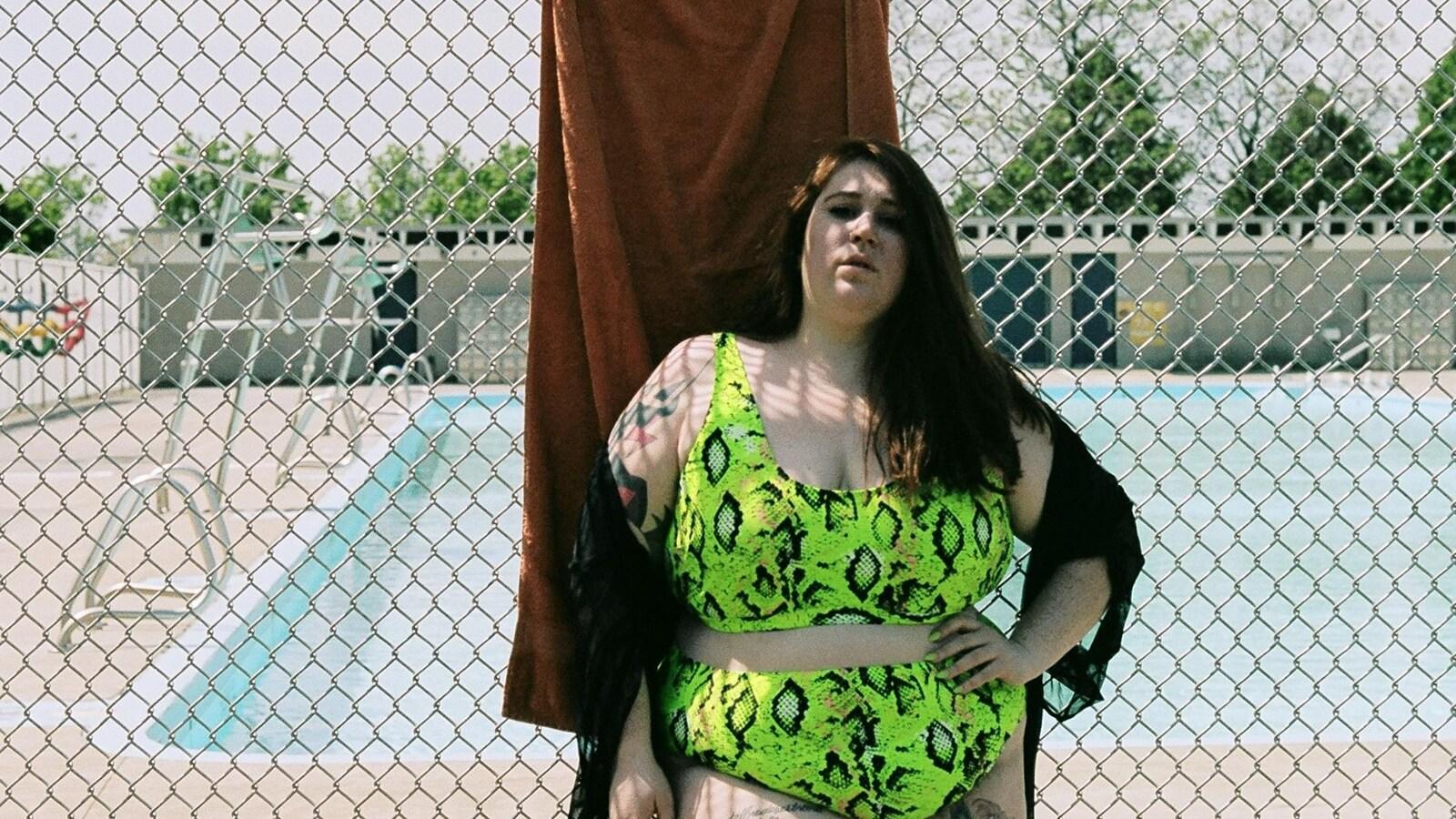 Une jeune femme pose en maillot deux pièces, vert fluo, devant la clôture métallique d'une piscine publique.