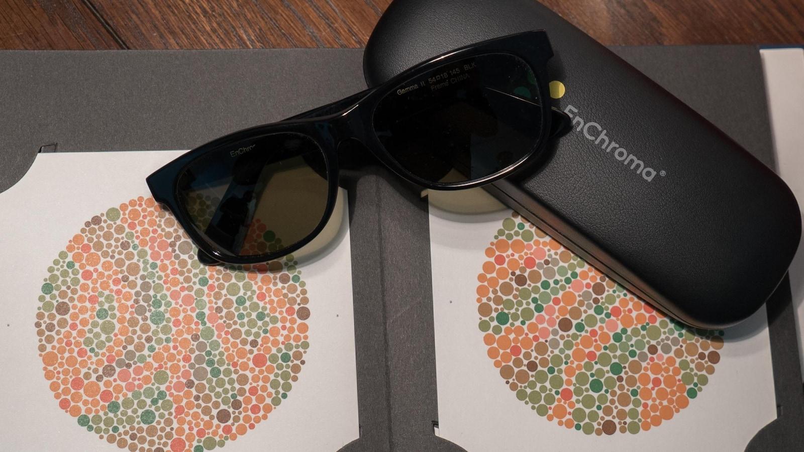 Une paire de lunettes foncées EnChroma déposées sur son étui et sur deux cercles d'un test d'Ishihara.