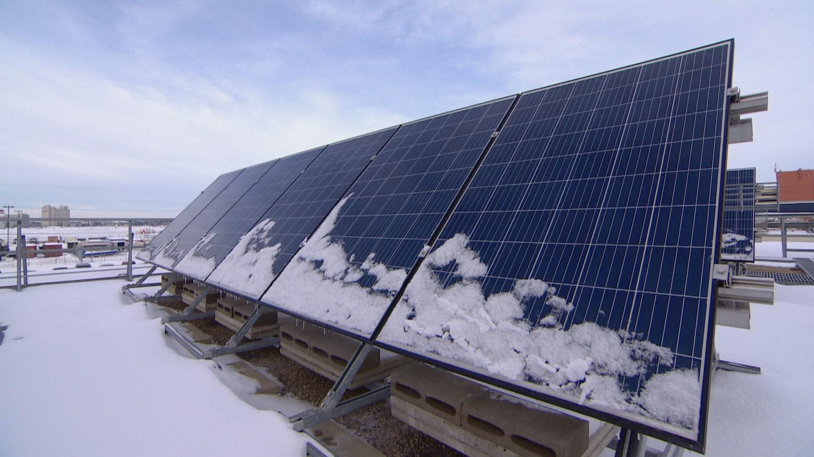 Des panneaux solaires sont installés de biais. Il y a de la neige dessus et autour.